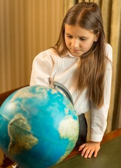 Portrait d'écolière mignonne regardant le globe terrestre