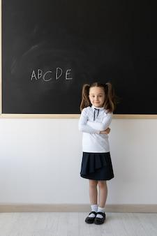 Portrait d'une écolière avec des nattes, l'apprentissage de l'alphabet