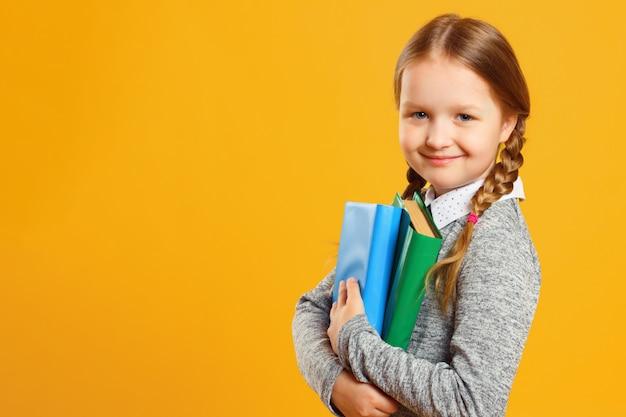 Portrait d'une écolière petite fille tenant des manuels scolaires.