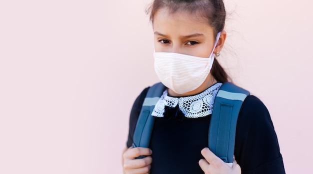 Portrait d'une écolière portant un masque médical sur le visage, sur fond rose.