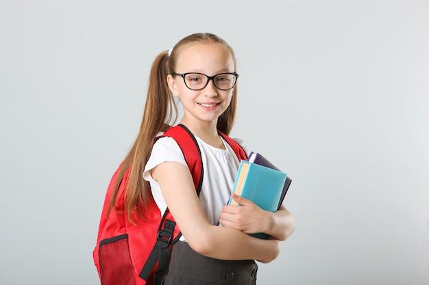 Portrait d'écolière avec un sac à dos et de la papeterie