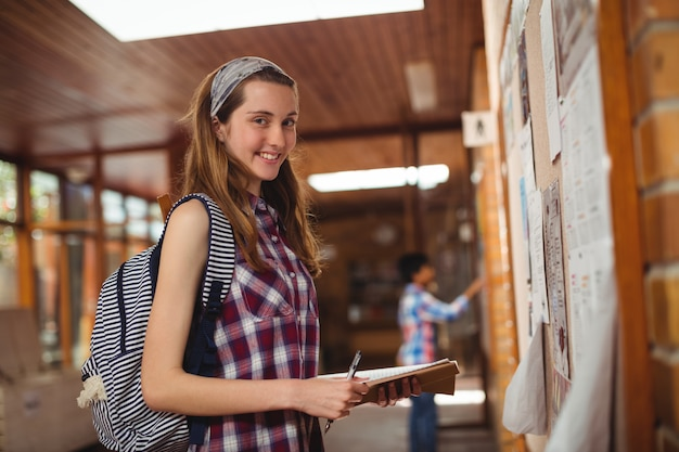 Portrait d'écolière souriante debout avec livre près de tableau d'affichage dans le couloir