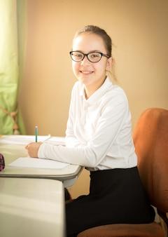 Portrait d'écolière souriante posant derrière la table en classe