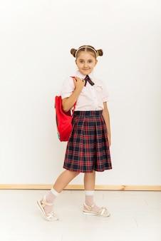 Portrait d'une écolière en uniforme debout sur fond blanc