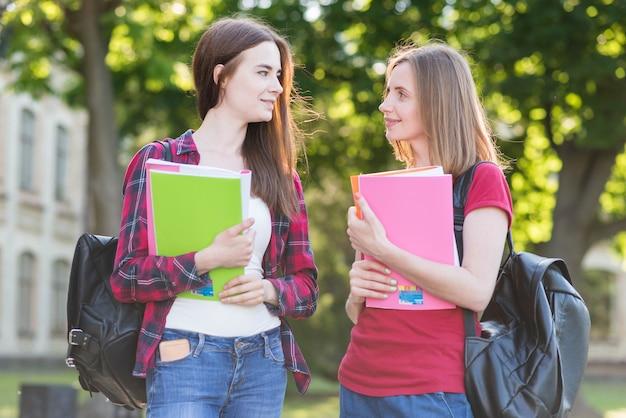 Portrait d'écolières avec des livres dans le parc
