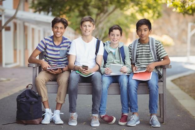Portrait d'écoliers à l'aide de téléphone mobile et tablette numérique sur banc dans le campus de l'école