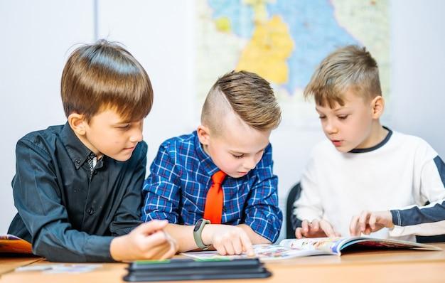 Portrait d'écoliers regardant des manuels avec d'autres élèves pendant une leçon dans une école intelligente moderne. mise au point sélective. vue de côté