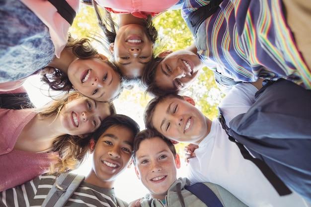 Portrait d'écoliers souriants formant une clique sur le campus