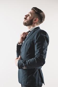 Portrait d'élégant beau jeune homme debout au studio contre le blanc.