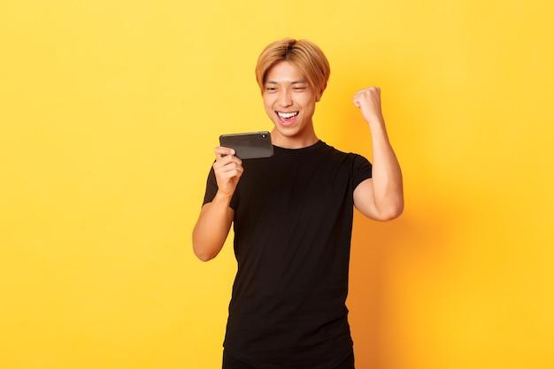 Portrait de l'élégant beau mec asiatique jouant au jeu smartphone
