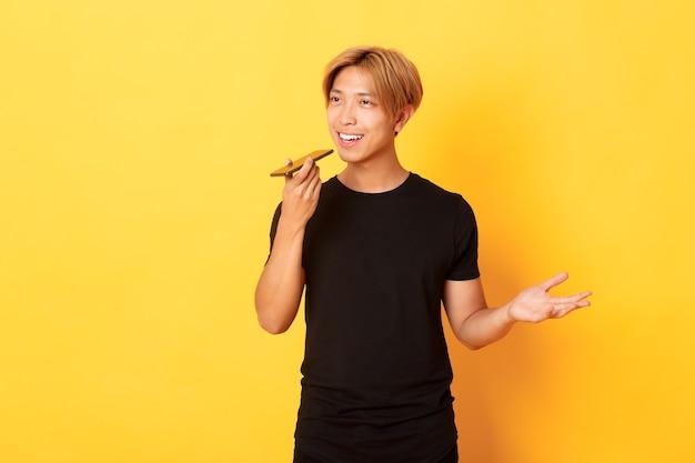 Portrait de l'élégant beau mec coréen aux cheveux blonds record message vocal sur téléphone mobile, tenant le smartphone près de la bouche et parlant, mur jaune debout