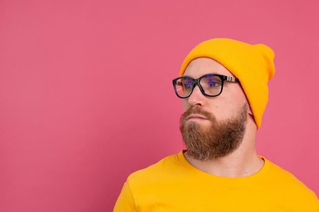 Portrait de l'élégant bel homme barbu européen en chapeau de chemise jaune décontracté et lunettes sur rose