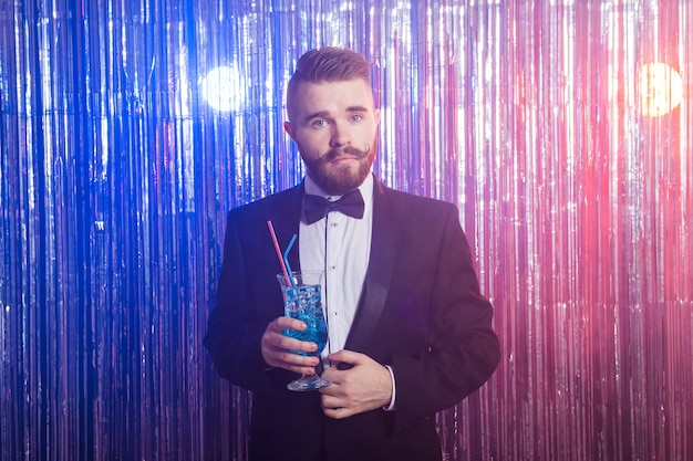 Portrait d'élégant bel homme buvant un cocktail