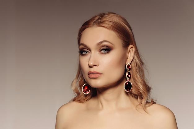Portrait élégant d'une femme moyenne avec de grandes boucles d'oreilles avec des pierres rouges