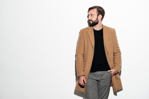 Portrait d'un élégant homme barbu habillé en manteau