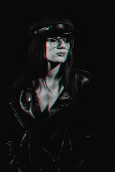 Portrait élégant d'une jeune fille avec des lunettes dans une veste en cuir et une casquette. anaglyphe noir et blanc avec effet de pépin de réalité virtuelle 3d