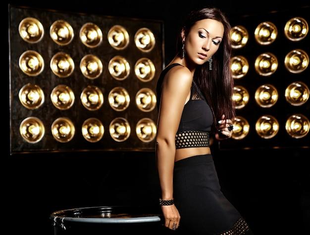 Portrait élégant d'un modèle de belle fille en vêtements noirs posant sur fond de lumières de studio noir