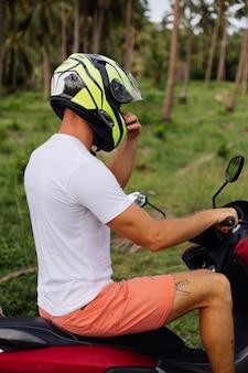 Portrait de l'élégant touriste masculin tatoué en lunettes de soleil, casque et chemise ouverte bleue sur moto