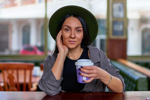 Portrait de l'élégant voyageur de femme hipster attrayant mignon buvant du café et assis à la boutique de café