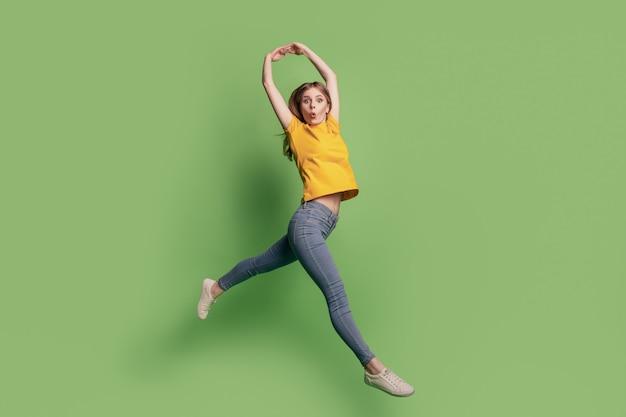 Portrait de l'élégante belle dame choquée saut danse ballet porter des baskets jeans t-shirt jaune sur fond vert
