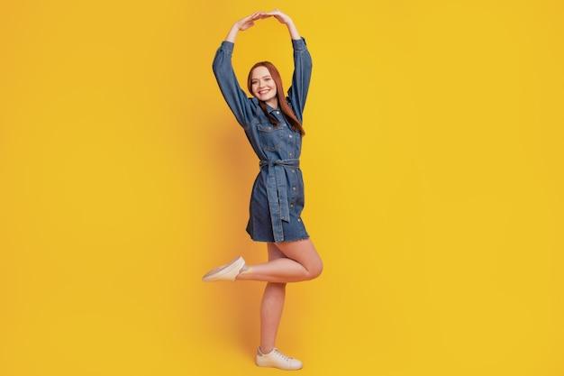 Portrait de l'élégante dame danse ballet porter des jeans mini robe chaussures sur fond jaune