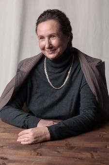 Portrait d'une élégante dame senior en costume assis près de la table.