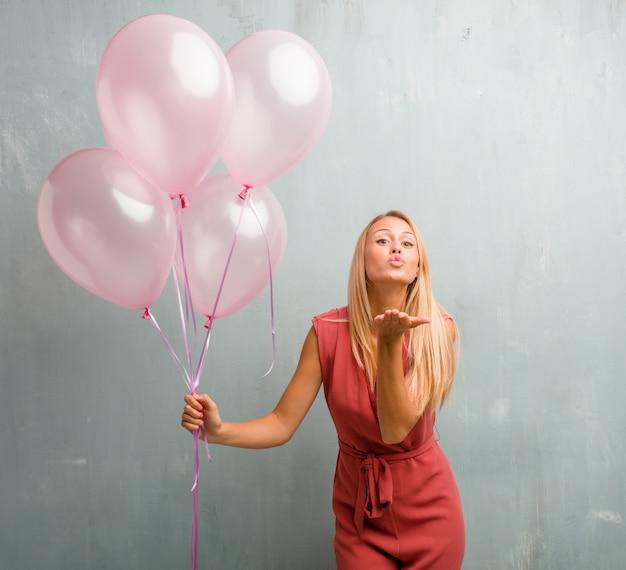 Portrait d'élégante jeune femme blonde envoie un baiser célébrant le nouvel an ou une autre veille