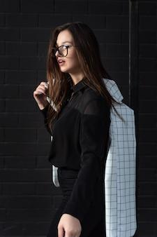 Portrait d'élégante jeune femme à lunettes et vêtements noirs sur fond noir. cadre vertical.