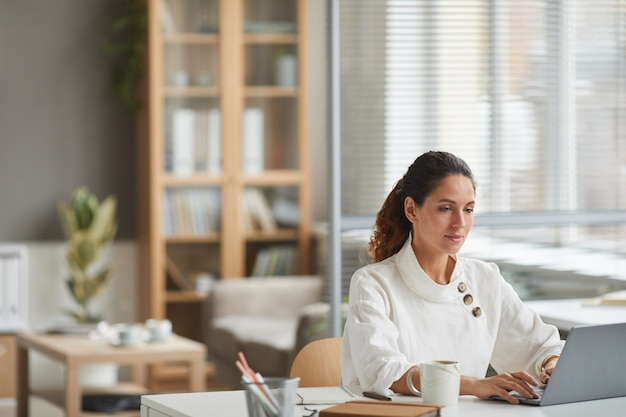 Portrait d'élégante jeune femme regardant écran d'ordinateur portable tout en appréciant le travail dans l'intérieur de bureau blanc, espace copie