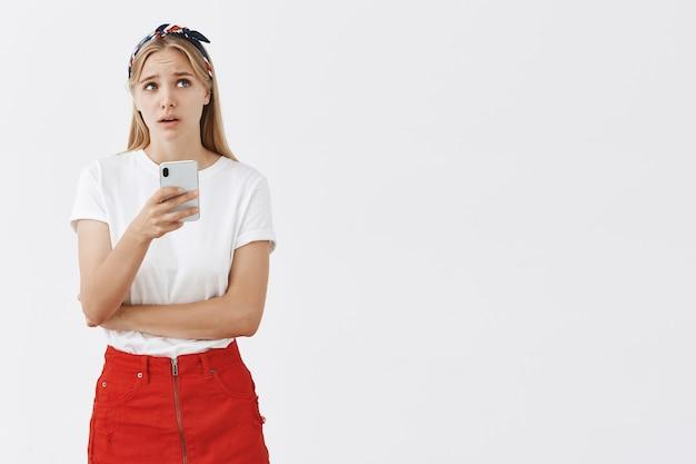 Portrait d'élégante jeune fille blonde posant contre le mur blanc