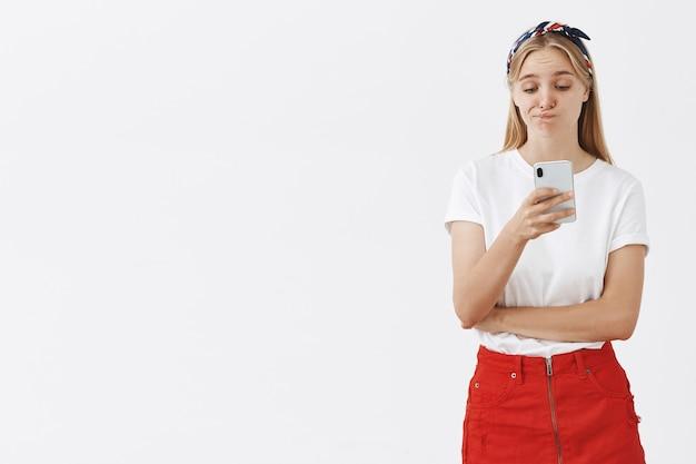 Portrait d'élégante jolie jeune fille blonde posant contre le mur blanc