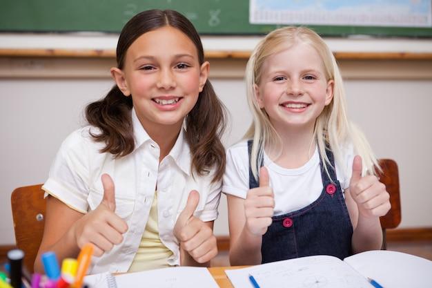 Portrait d'élèves heureux travaillant avec le pouce en l'air