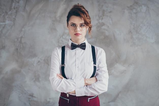 Portrait d'elle, elle a l'air bien habillée jolie jolie fille sérieuse aux cheveux ondulés, les bras croisés isolés sur fond de mur industriel en béton gris