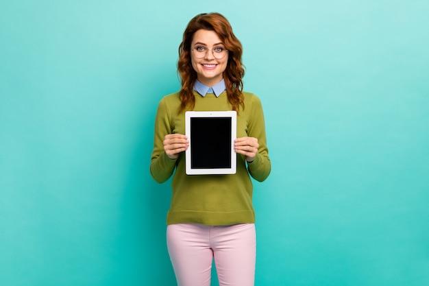 Portrait d'elle, elle a un beau contenu attrayant, une fille aux cheveux ondulés gaie et gaie, tenant dans les mains un nouveau produit de tablette isolé sur un fond de couleur turquoise turquoise vif et brillant