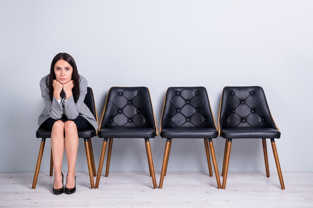 Portrait d'elle elle belle attrayante chic ennuyée dame qualifiée directrice des ventes assise sur une chaise en attente de réunion recruteur appliquer un arrière-plan de couleur gris pastel isolé