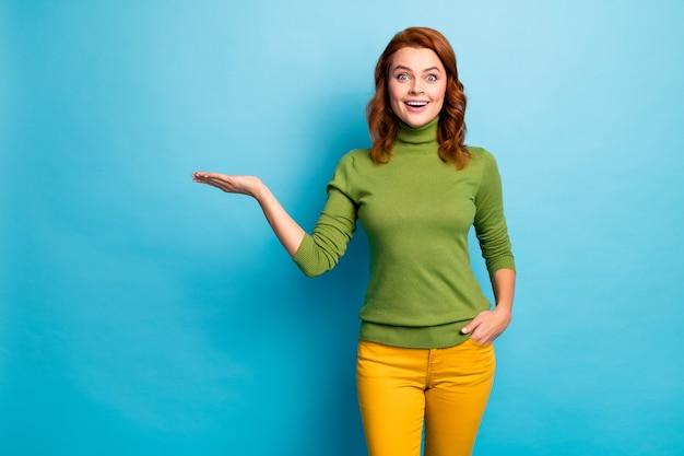 Portrait d'elle elle belle attrayante étonné étonné joyeux joyeux joyeux heureux fille aux cheveux ondulés tenant sur la paume nouvelle nouveauté isolée sur un mur de couleur turquoise bleu turquoise vif éclat vif