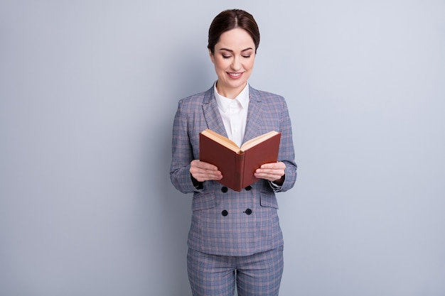 Portrait d'elle, elle a une belle enseignante gaie, attirante, concentrée, compétente et intellectuelle, vêtue d'un costume à carreaux décontracté, lisant un dictionnaire académique isolé sur fond de couleur pastel gris