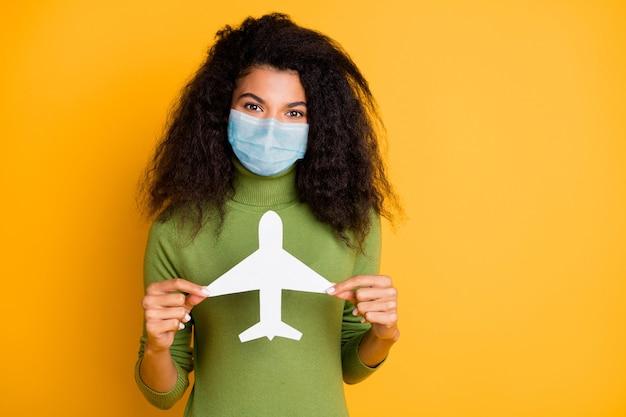 Portrait d'elle elle belle fille aux cheveux ondulés portant un masque de gaze de sécurité arrêter la grippe wuhan mers cov tenant dans un avion en papier à la main isolé brillant vif fond de couleur jaune vif
