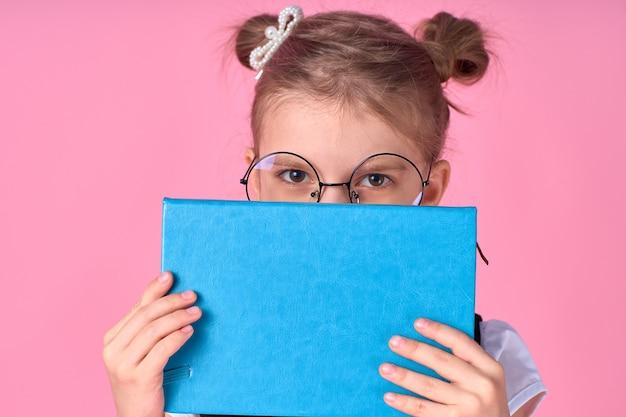 Portrait d'elle elle belle foxy belle attrayante joyeuse écolière positive tenant dans les mains se cachant derrière le livre ouvert préparation à l'examen isolé sur l'espace rose