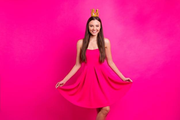 Portrait d'elle elle belle jolie belle belle fille aux cheveux longs joyeuse joyeuse portant une robe de couronne posant isolé sur fond de couleur rose fuchsia brillant vif éclatant