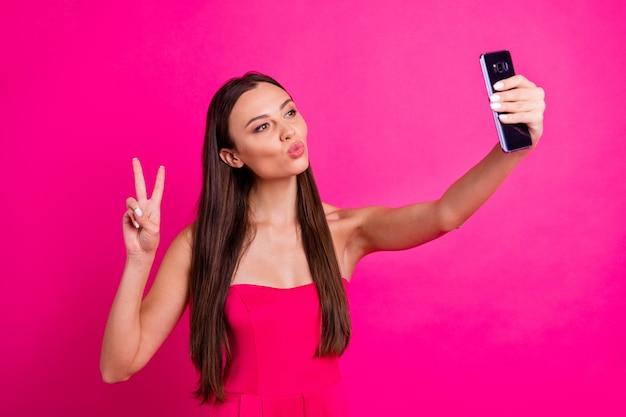 Portrait d'elle elle belle jolie fille aux cheveux longs joyeuse joyeuse faisant selfie montrant v-sign envoi baiser isolé sur fond de couleur rose fuchsia brillant vif éclatant