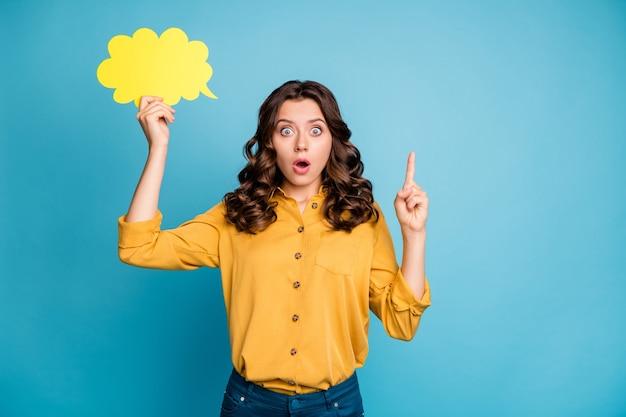 Portrait d'elle elle belle jolie fille aux cheveux ondulés étonné tenant en mains la carte de l'espace copie jaune pointant vers le haut.