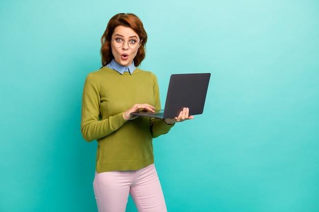 Portrait d'elle, elle belle jolie fille aux cheveux ondulés joyeuse émerveillée tenant dans les mains un ordinateur portable naviguant sur un site web isolé sur un fond de couleur turquoise turquoise vif éclatant
