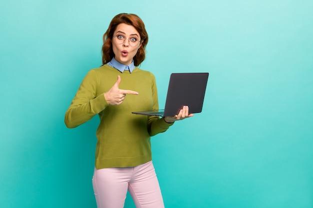 Portrait d'elle, elle belle jolie fille aux cheveux ondulés joyeuse étonnée tenant dans les mains un ordinateur portable démontrant un nouveau service isolé sur fond de couleur turquoise sarcelle vibrant éclatant vif
