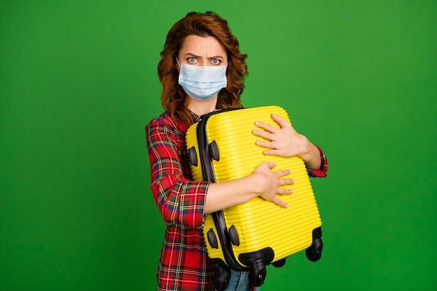 Portrait d'elle elle belle jolie fille aux cheveux ondulés sombre et maussade portant un masque de gaze embrassant la valise tourisme dangereux isolé sur fond de couleur vert vif brillant éclatant