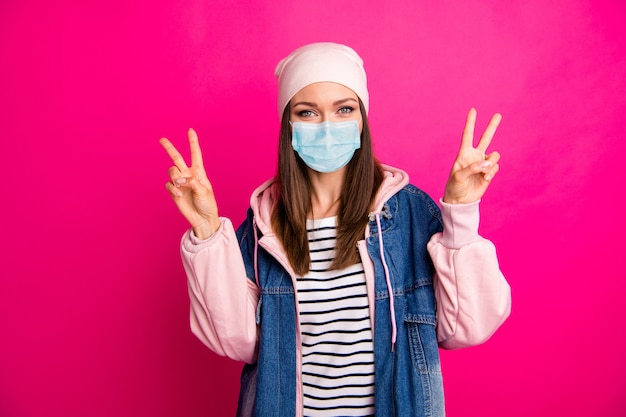 Portrait d'elle elle belle jolie fille funky montrant double v-sign mers cov décontamination maladie maladie prévention de la maladie isolée sur fond de couleur rose fuchsia vif brillant éclatant