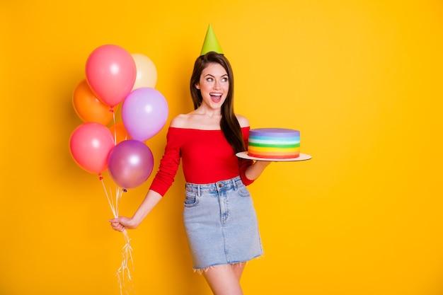 Portrait d'elle elle belle jolie fille joyeuse assez gaie tenant dans la main des boules d'hélium de gâteau fait maison s'amusant événement festif isolé brillant vif éclat vibrant fond de couleur jaune
