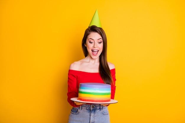 Portrait d'elle elle belle jolie jolie fille joyeuse et gaie tenant dans les mains un gâteau rayé s'amusant occasion de fête isolé brillant vif éclat vibrant fond de couleur jaune