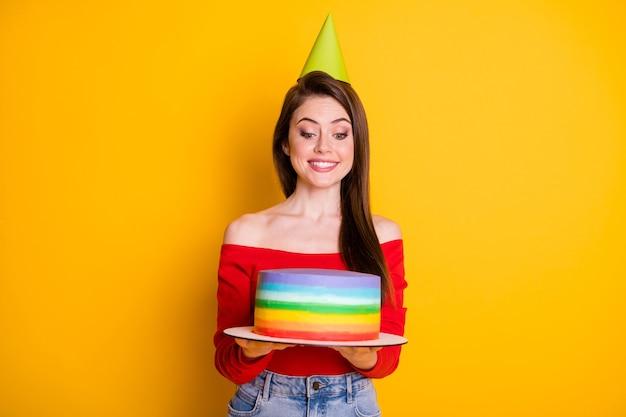 Portrait d'elle elle belle jolie jolie fille joyeuse gaie tenant dans les mains un gâteau savoureux frais fait maison à rayures isolées fond de couleur jaune vif éclat vif éclatant