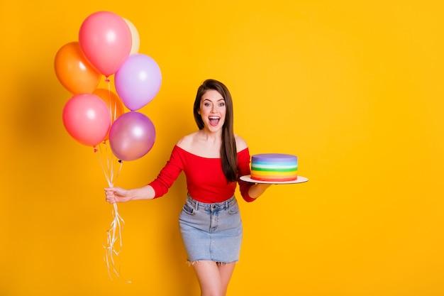 Portrait d'elle elle belle jolie jolie fille joyeuse joyeuse tenant à la main des boules d'hélium de gâteau frais s'amusant féliciter isolé brillant vif éclat vibrant fond de couleur jaune